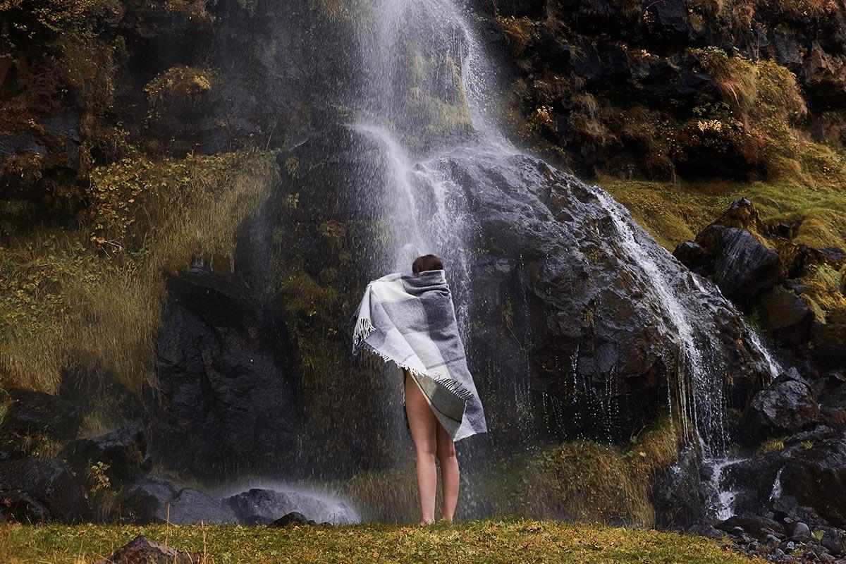 Anne Moldenhauer, Modell mit Decke vor Wasserfall, Island